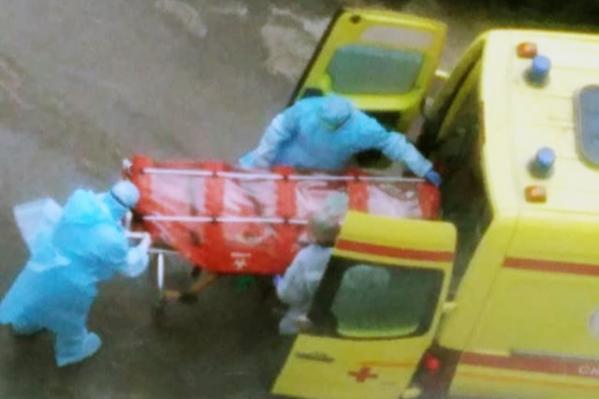 Врачи в защитных костюмах грузят человека в капсуле в автомобиль скорой помощи