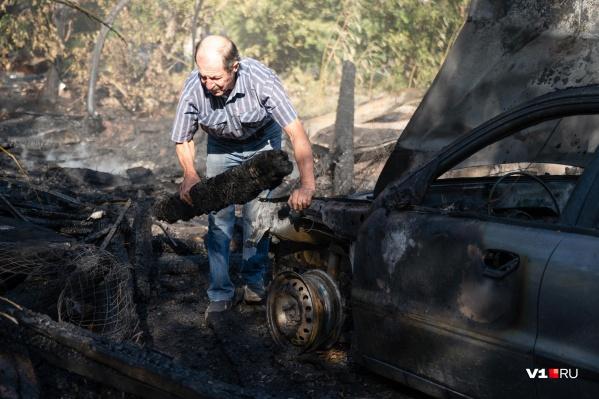 Пенсионер освобождает свою машину от обломков сгоревшей постройки
