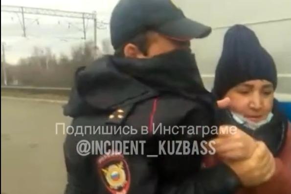 Сотрудник полиции пытался запихнуть женщину в патрульную машину