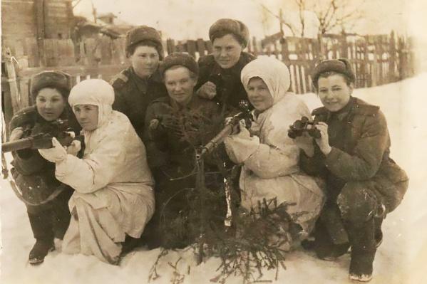 Анна Кошевая (вторая слева, в зимнем костюме и со снайперской винтовкой в руках) с подругами во время войны