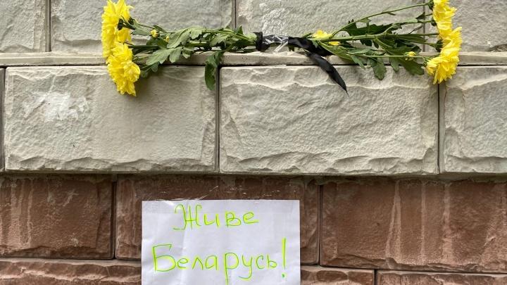 Люди несут цветы к представительству Белоруссии в Тюмени