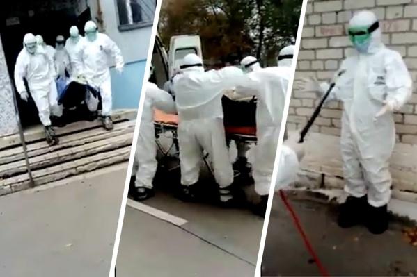 Заболевшего переносят на носилках в карету скорой помощи