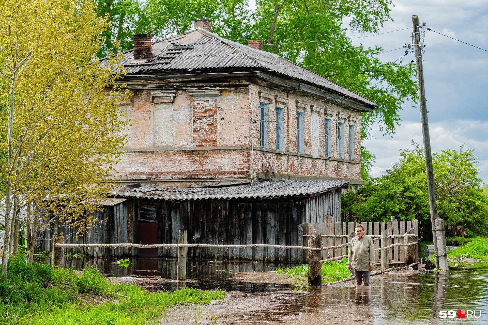 Ольга у своего залитого водой дома