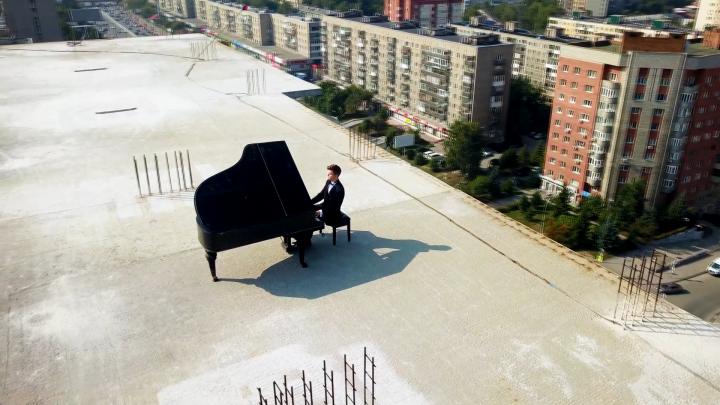 На крышу строящейся высотки на Красном проспекте подняли рояль — зачем он там и кто на нём играет. Смотрим вместе