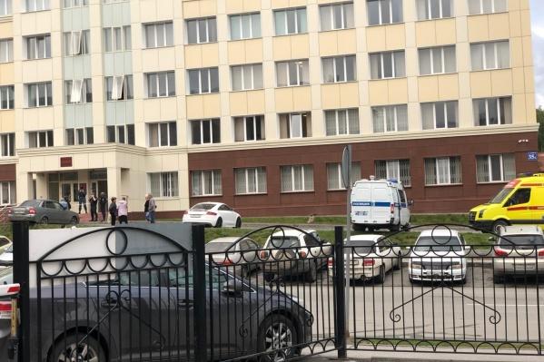 Так выглядела территория Заельцовского суда этим утром. На парковке — машины полиции и скорой, у входа в недоумении стоят люди
