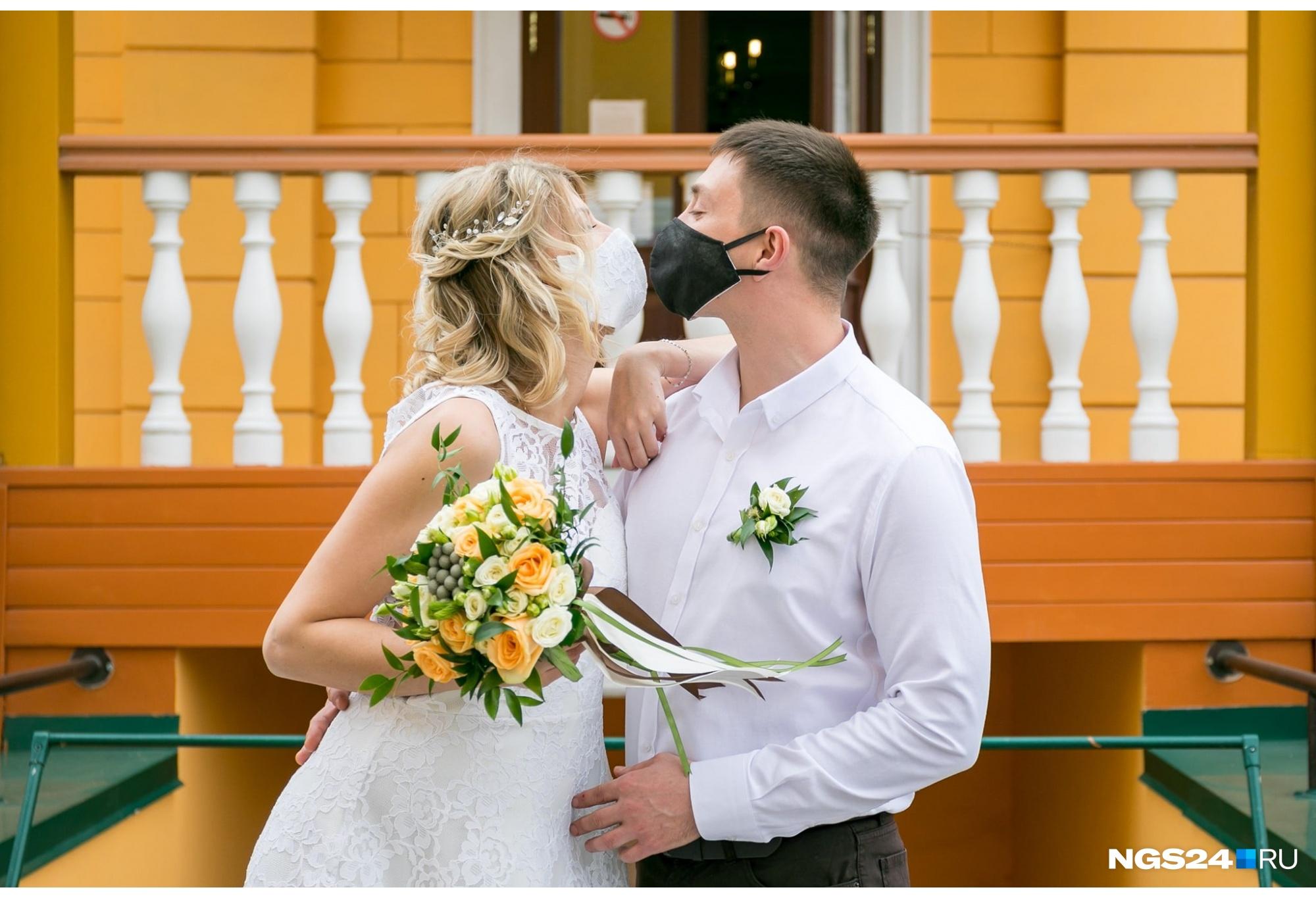 Даже привычные праздники в этом году шли не по сценарию. Это фото сделано у Дома семейных торжеств в Красноярске. В первую волну ковида парам предлагали перенести регистрацию на осень. Влюбленные расписывались в масках, без гостей