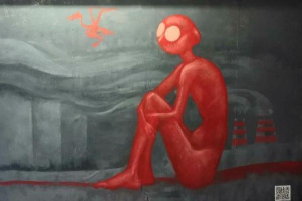 Красный человечек смотрит на скелет птицы