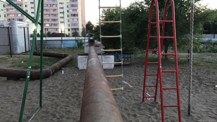 В омском дворе трубу от теплотрассы протянули сквозь детскую площадку и огородили забором