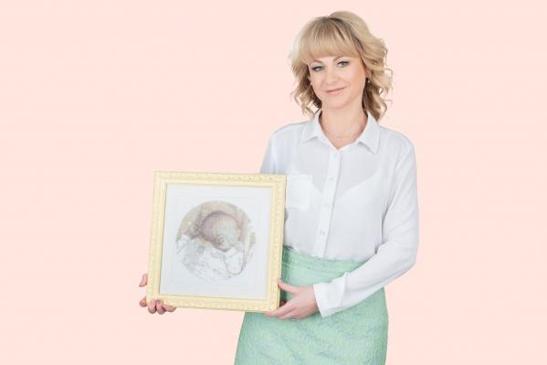 Наталья  Воронова, ведущий репродуктолог «Клиники Пасман» с картиной, которую ей  подарила пациентка, — эту вышивку она сделала 10 лет назад и дала зарок  подарить ее доктору, который сможет помочь ей родить ребёнка