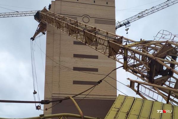 Один из башенных кранов упал на здание. Внутри, судя по всему, находился рабочий — крановщик