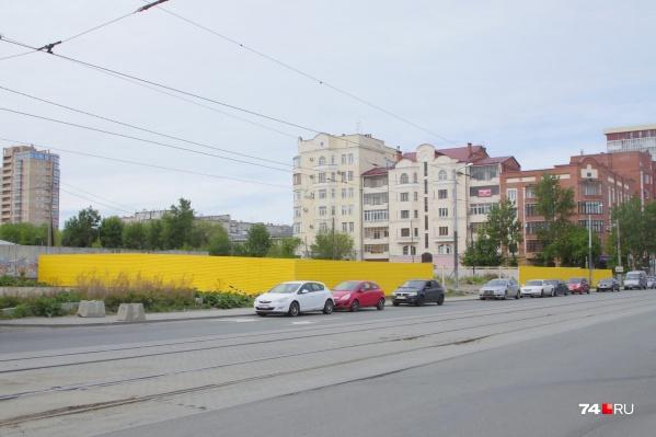 Место, где ещё недавно парковали машины работники соседних офисов, огородили ярко-жёлтым забором