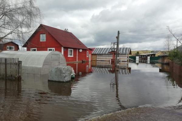 Вода затопила огороды, передвигаются жители по таким участкам на моторных лодках
