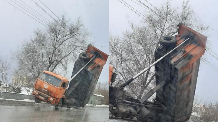 В Самаре КАМАЗ кузовом снес световую опору и повис на проводах