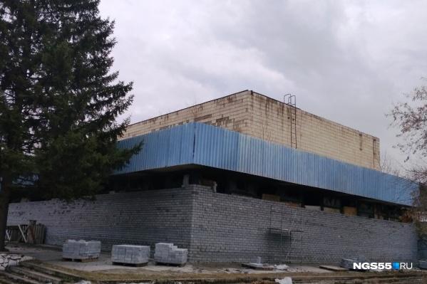 В прошлом году после пожара вокруг здания возвели кирпичную стену, а окна и двери заварили