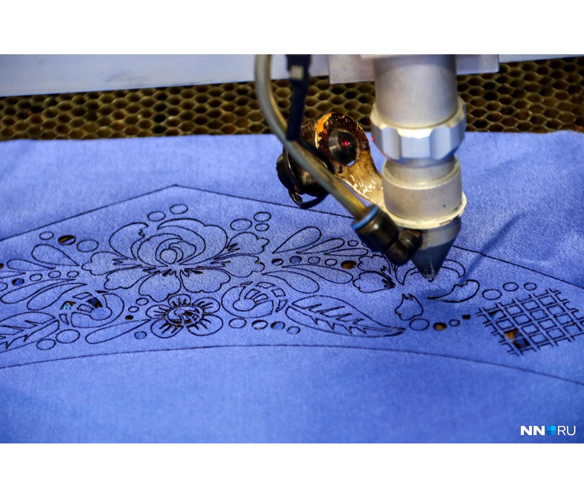 Лазер вырезает на ткани мелкие фигуры по заданному в программу узору