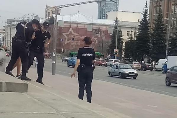 Парня увели за руки и посадили в полицейскую машину