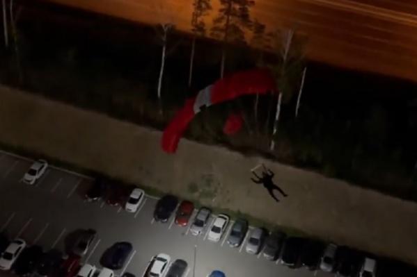 Парашютист пролетел над парковкой