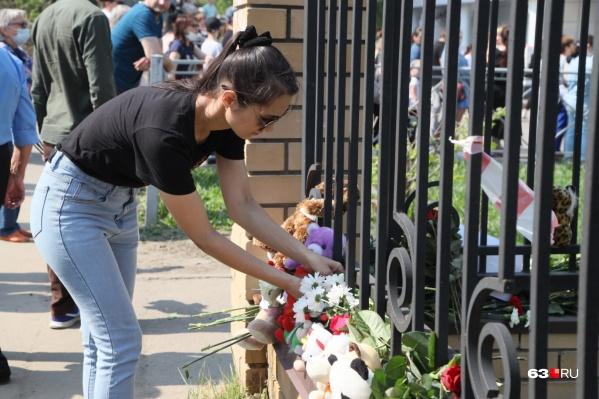 К школе, где погибли и пострадали дети, продолжают нести цветы и игрушки