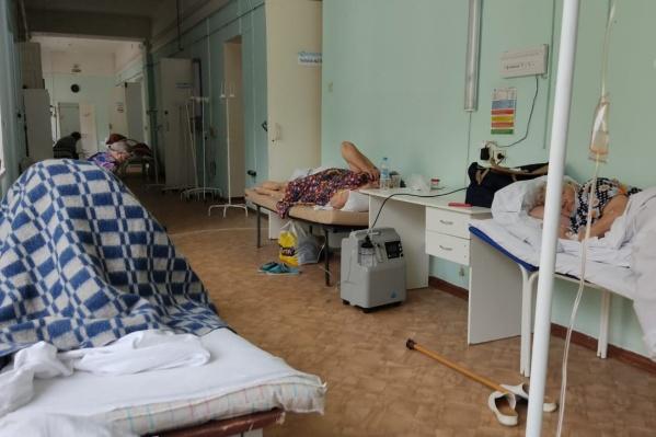 Пациенты лежат на кушетках в коридоре горбольницы и ждут, когда в палатах освободятся места