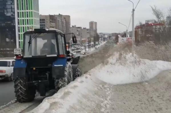 Трактор выбросил снег с дороги на тротуар
