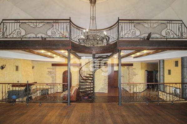 В гостиной можно устроиться на нижнем ярусе или смотреть на всё свысока в прямом смысле слова: достаточно подняться по витой лестнице