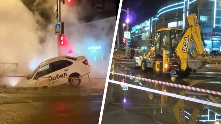 В Екатеринбурге такси провалилось под асфальт посреди дороги, из огромной ямы хлещет кипяток. Видео