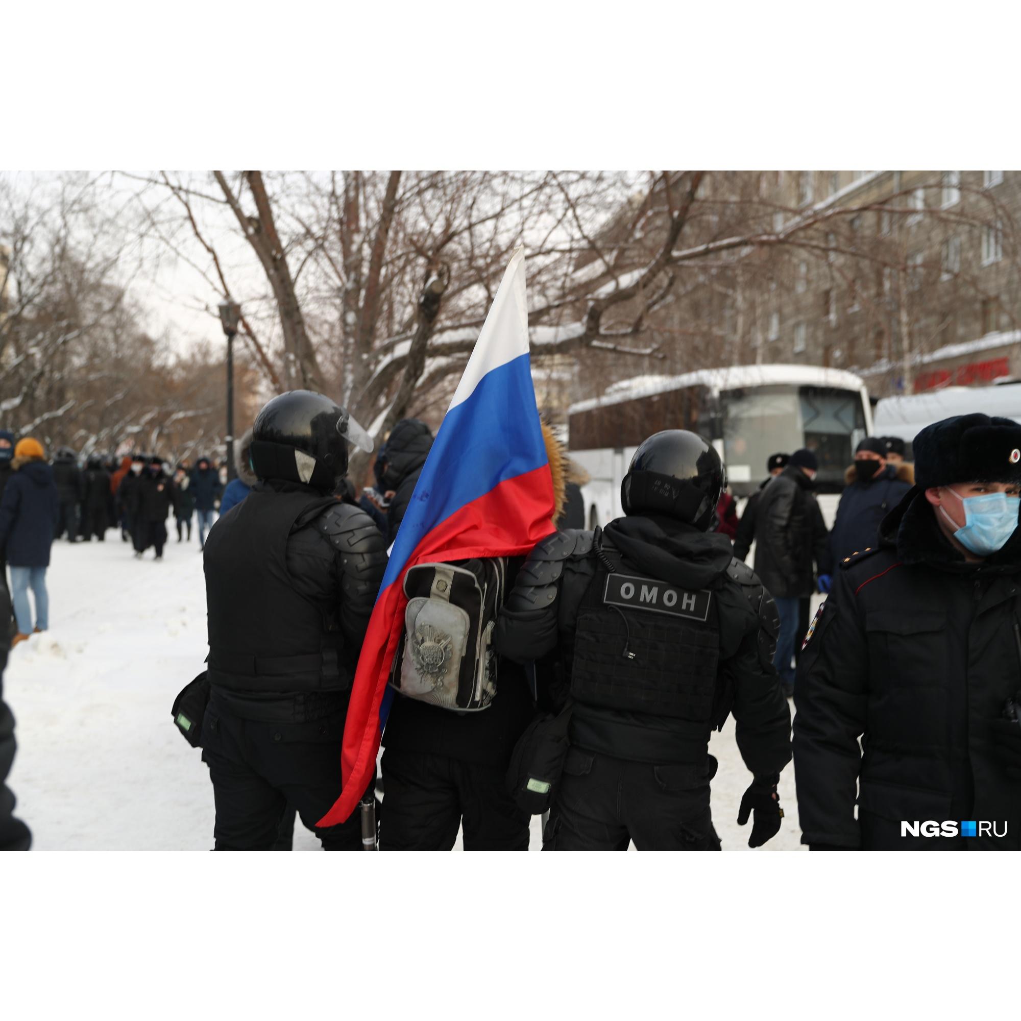 Сотрудники ОМОНа уводят участника акции с российским флагом