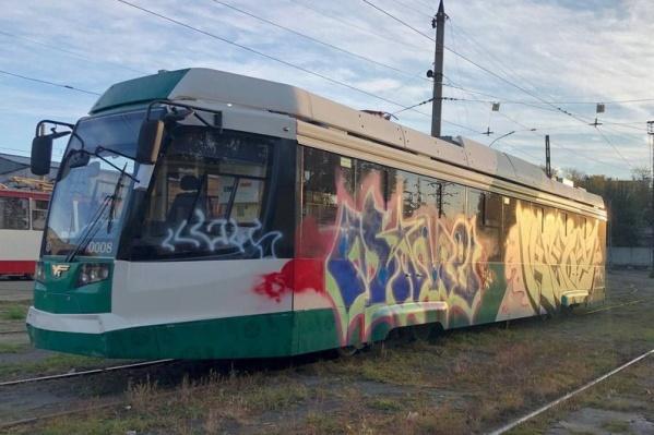Непонятными граффити разукрасили бока и стекла бело-зеленого вагона