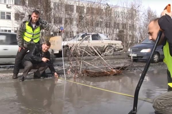 Анатолий Локоть (на тот момент еще кандидат в мэры Новосибирска) измеряет ямы