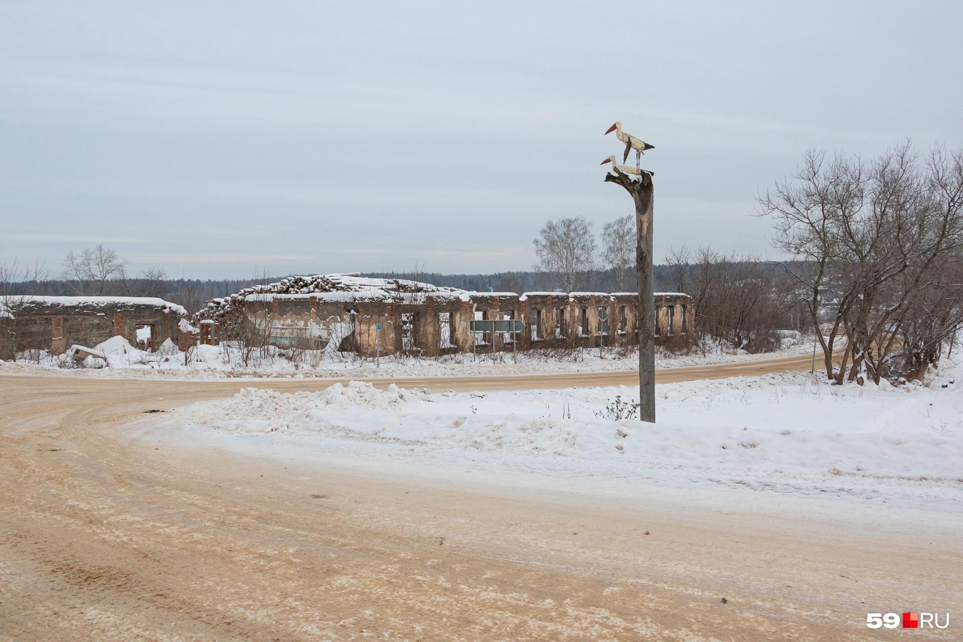 На окраине поселка — деревянные аисты и руины. Когда-то здесь была картонная фабрика
