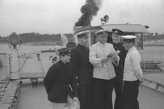 """Это фото было сделано 13 сентября 1957 года. На нем запечатлены члены команды парохода «<nobr class=""""_"""">А. Серафимович</nobr>» (слева направо): масленщик <nobr class=""""_"""">А. А. Федняев</nobr>, 1-й штурман <nobr class=""""_"""">Н. Н. Нужин</nobr>, капитан судна <nobr class=""""_"""">Д. П. Савельев</nobr>, 2-й помощник механика <nobr class=""""_"""">В. А. Романов</nobr>, 2-й штурман <nobr class=""""_"""">А. П. Осипов</nobr>"""