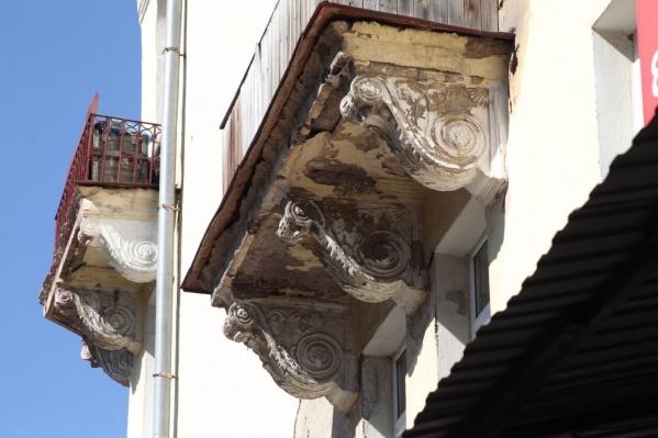 Сейчас рабочие сбивают молотком кронштейны, которые расположены под балконами