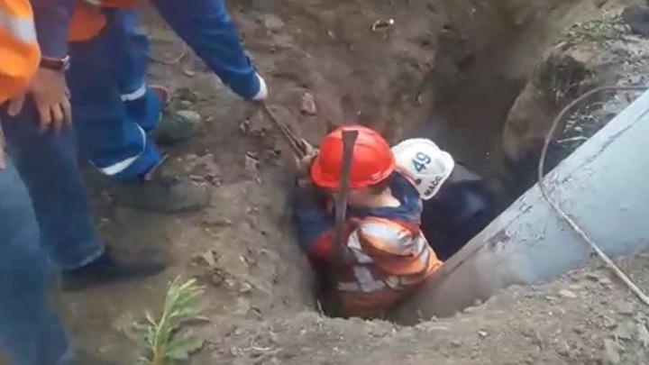 Молодого рабочего зажало столбом в яме — видео, на котором мужчину откапывают коллеги и спасатели