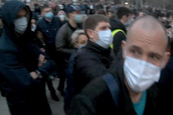 Олега Орлова (справа крупным планом) засняли на площади перед администрацией края в толпе протестующих
