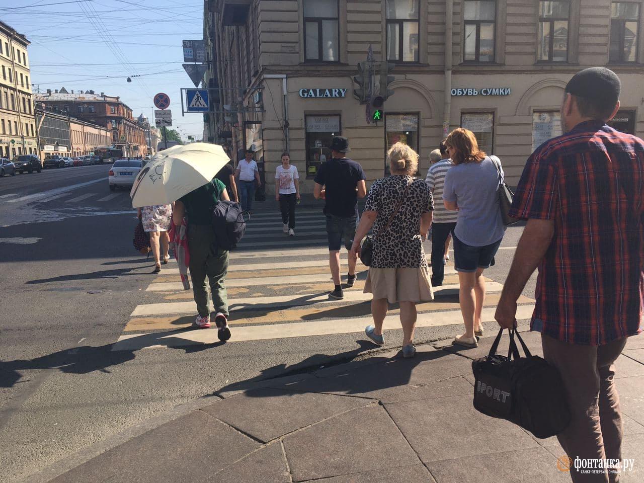 Петербуржцы прячутся от палящего солнца под зонтиками.