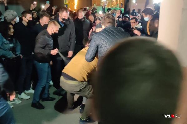 Полицейский в штатском старательно поливает газом лежащих на асфальте задержанных