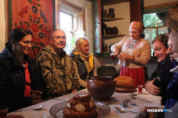 На экскурсии по «Старине Сибирской» в избах гостей угощают кашей хозяйки
