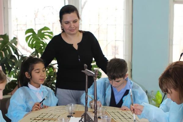 На занятиях Татьяна Маянская учит школьников рисовать иероглифы на рисовой бумаге