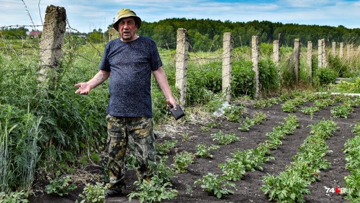 Николай Шермин стоит на краю своего огорода вдоль старой колючки, ограждающей пойму Течи от людей