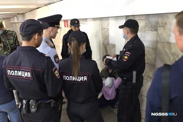 Мужчина с ребенком в подземном переходе. Напротив него в белой рубашке — курсант МВД, который смог обезоружить омича