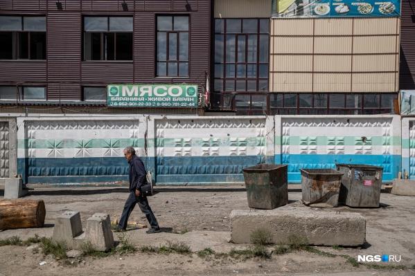 На фасаде трехэтажного торгового центра еще остаются вывески десятка компаний, которые в нем работали, но доступ в него уже перекрыли строительным забором