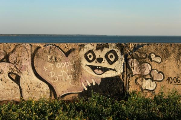 Стену вдоль моря украшают граффити с разным настроением