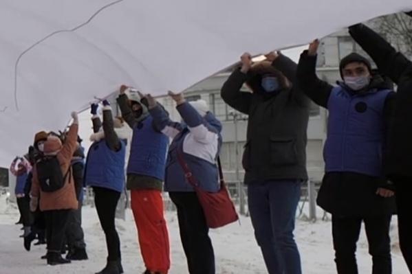 На этом скриншоте видно, что несколько человек, участвовавших в акции с триколором, были в одинаковых синих жилетках<br>