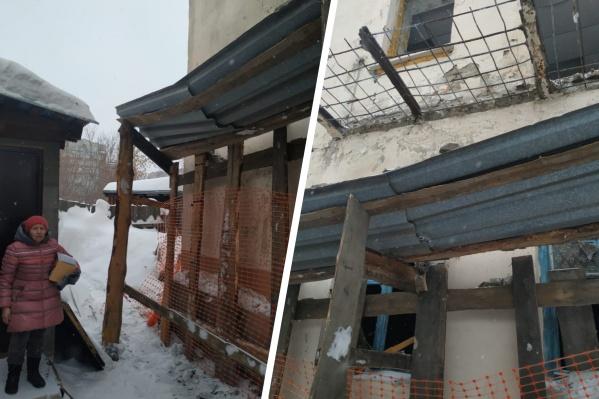 Крыша навеса, установленного рабочими на участке, уже прогнулась под тяжестью падающих сверху строительных конструкций