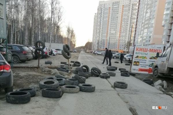 Дорогу из бетонных плит перегородили покрышками, но жители быстро расправились с этой изгородью