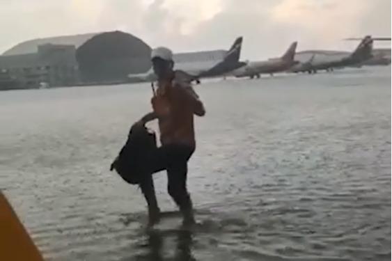 Чтобы попасть в аэропорт, людям приходится идти по стихийной реке