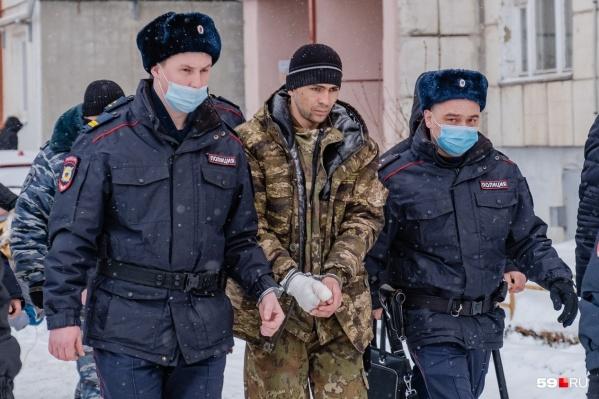 Супруга убитой (он в центре) почти сразу задержали по подозрению в преступлении