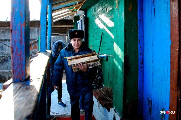 Виталий Ибрагимов поднимается на крыльцо с дровами — отопление печное