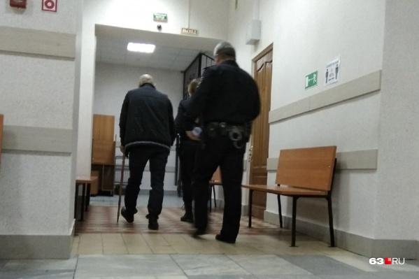 Сергей Кузьмин (слева) старался скрыть лицо от камер