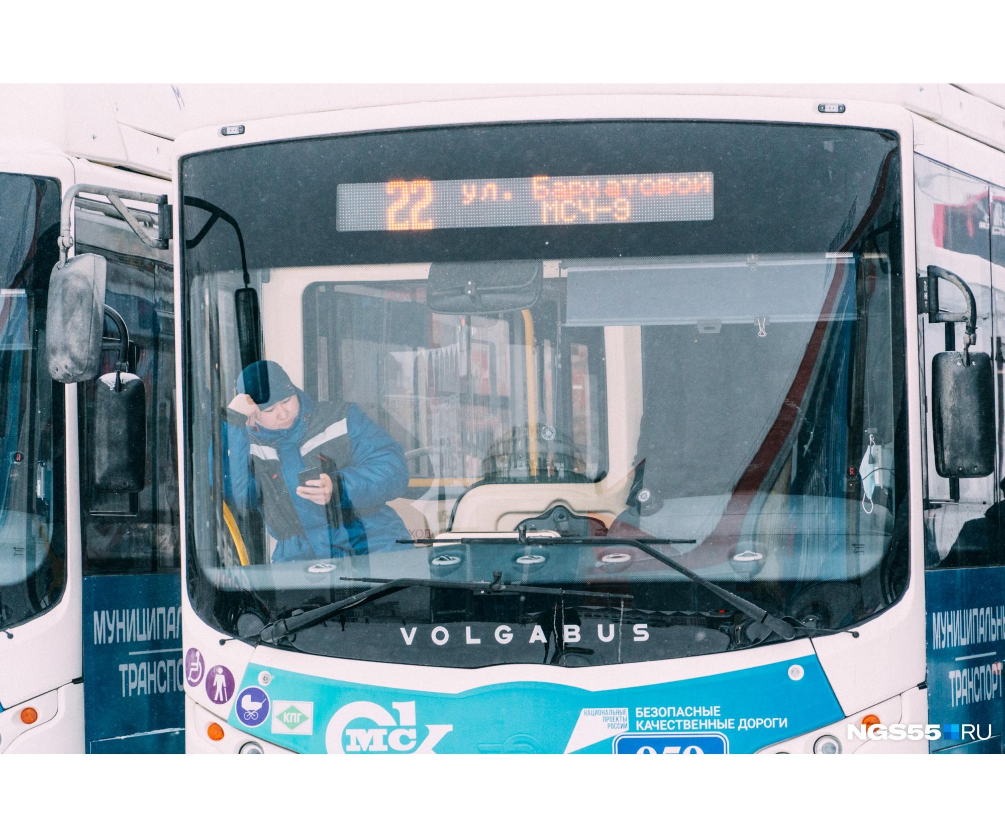 В ожидании презентации водитель одного из автобусов внимательно изучает телефон